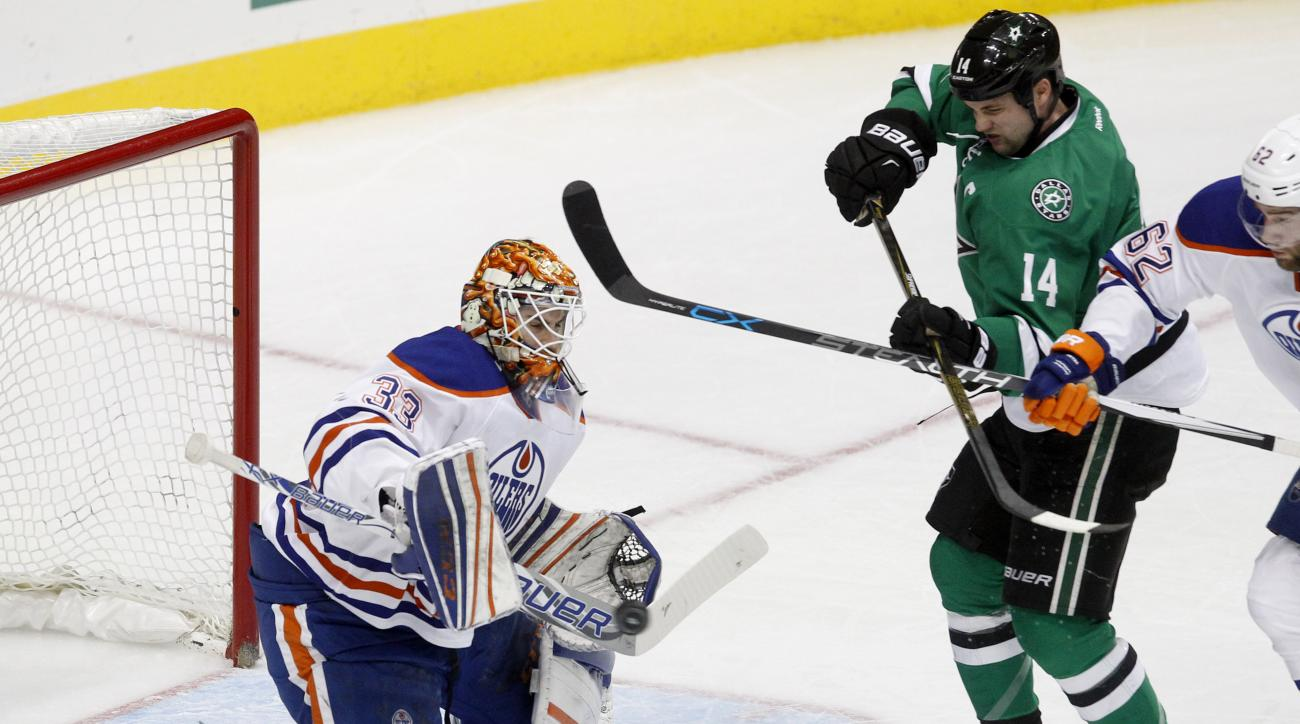 CORRECTS TO THURSDAY NOT FRIDAY - Edmonton Oilers goalie Cam Talbot (33) stops the puck as he is pressured by Dallas Stars left wing Jamie Benn (14) during the first period of an NHL hockey game Thursday, Jan. 21, 2016, in Dallas. (AP Photo/Tim Sharp)