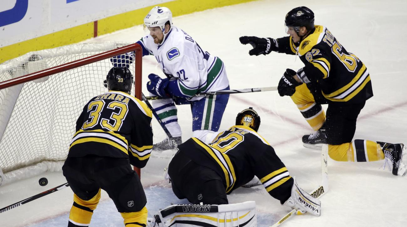 Vancouver Canucks left wing Daniel Sedin (22) scores against Boston Bruins goalie Tuukka Rask (40) as Bruins defensemen Zdeno Chara (33) and Zach Trotman (62) try to prevent the goal during the third period of an NHL hockey game, Thursday, Jan. 21, 2016,
