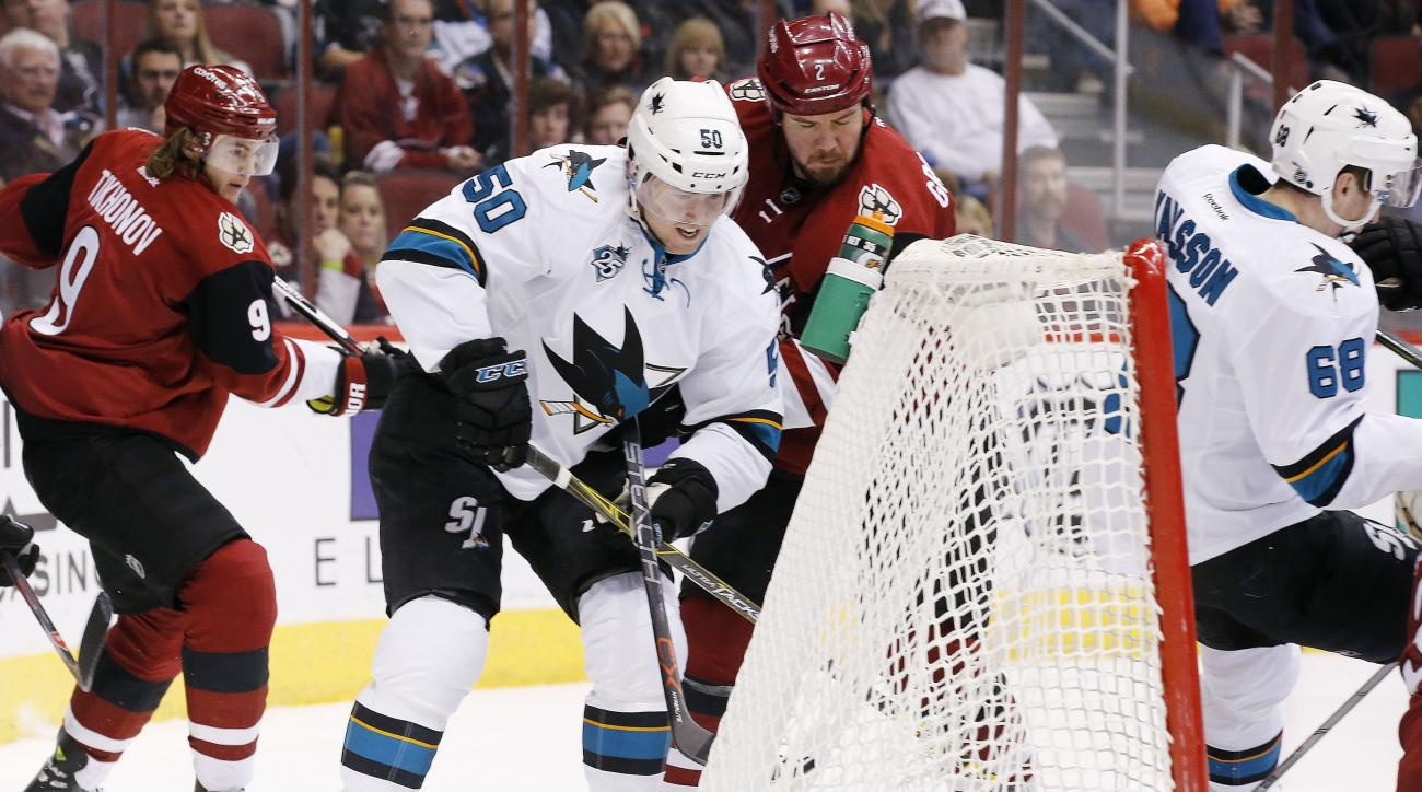 San Jose Sharks' Chris Tierney (50) stuffs the puck in for a goal as Arizona Coyotes' Nicklas Grossmann (2), of Sweden, and Viktor Tikhonov (9), of Russia, defend and Sharks' Melker Karlsson (68), of Sweden, falls into the goal during the first period of