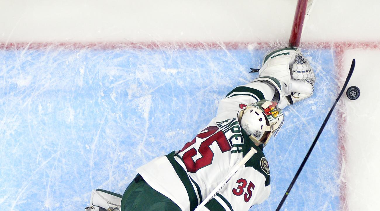 Los Angeles Kings center Tyler Toffoli, right, tries to get a shot in on Minnesota Wild goalie Darcy Kuemper during the first period of an NHL hockey game Thursday, Jan. 21, 2016, in Los Angeles. (AP Photo/Mark J. Terrill)