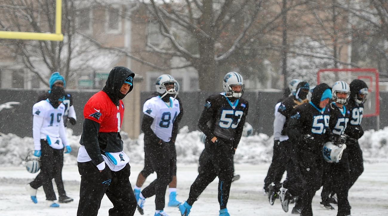 Carolina Panthers quarterback Cam Newton, left, walks across a practice field covered in snow and ice, Friday, Jan. 22, 2016, in Charlotte, N.C. The Panthers host the Arizona Cardinals in the NFC championship NFL football game on Sunday. (Jeff Siner/The C