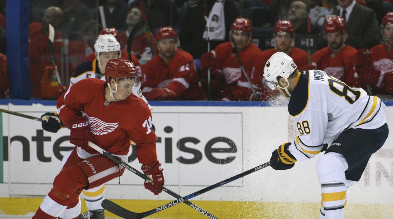 Detroit Red Wings' Dylan Larkin (71) vies for the puck with Buffalo Sabres' Jamie McGinn (88) during the first period of an NHL hockey game Friday, Jan. 22, 2016 in Buffalo, N.Y. (AP Photo/Gary Wiepert)