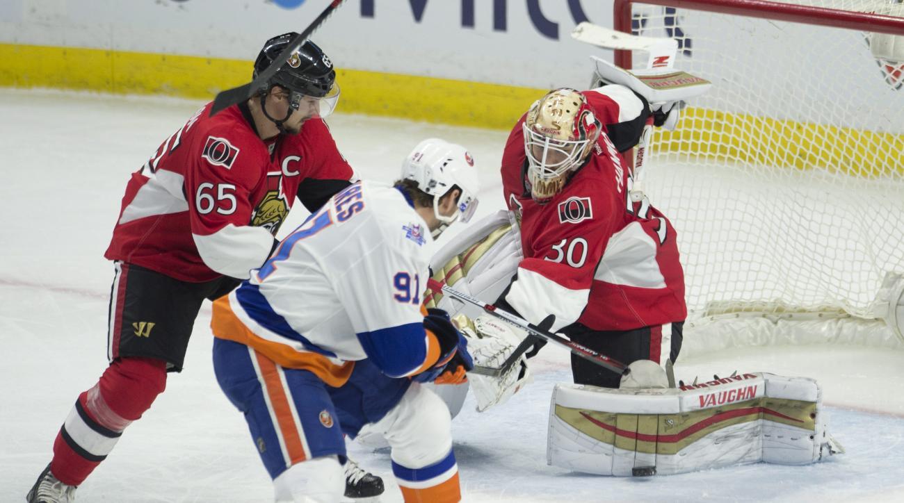 Ottawa Senators goalie Andrew Hammond, right, kicks out a shot to New York Islanders center John Tavares (91) who scored on the rebound as Senators defenseman Erik Karlsson (65) looks on during third-period NHL hockey game action Friday, Jan. 22, 2016, in