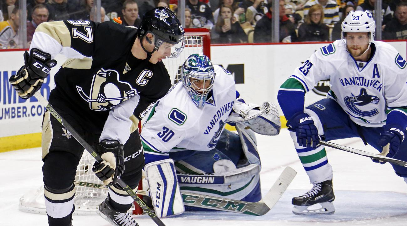 Pittsburgh Penguins' Sidney Crosby (87) looks to get off a shot in front of Vancouver Canucks goalie Ryan Miller (30) and Alexander Edler (23) during the second period of an NHL hockey game in Pittsburgh, Saturday, Jan. 23, 2016. (AP Photo/Gene J. Puskar)