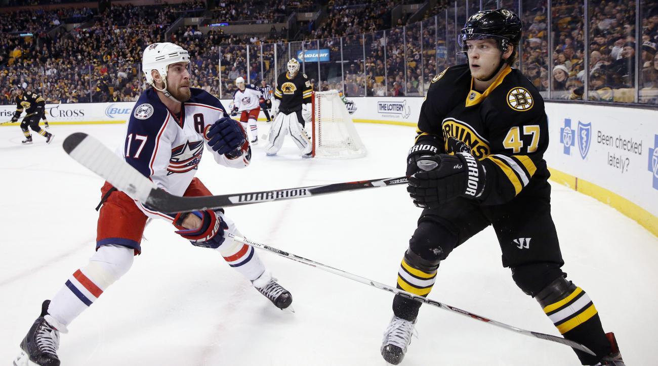 Boston Bruins' Torey Krug (47) sends the puck along the boards as Columbus Blue Jackets' Brandon Dubinsky (17) skates in during the first period of an NHL hockey game in Boston, Saturday, Jan. 23, 2016. (AP Photo/Michael Dwyer)