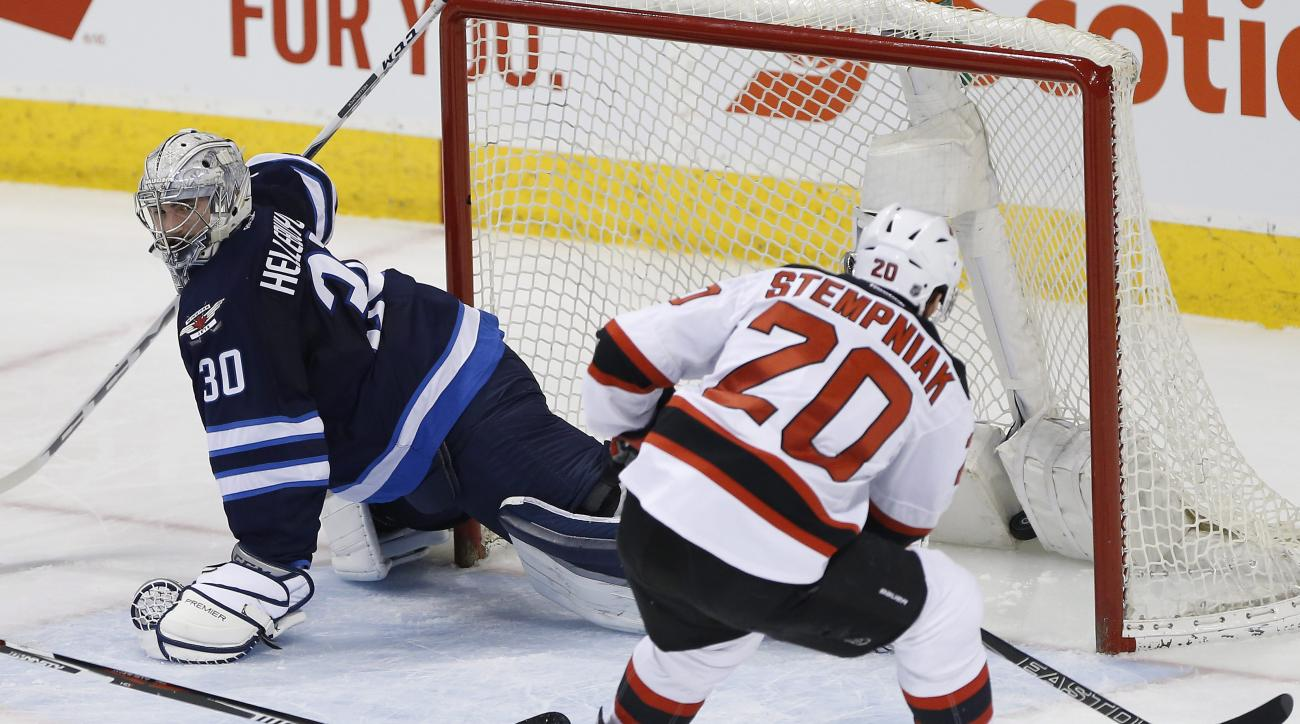 New Jersey Devils' Lee Stempniak (20) scores on Winnipeg Jets goaltender Connor Hellebuyck (30) during the first period of an NHL hockey game Saturday, Jan. 23, 2016, in Winnipeg, Manitoba. (John Woods/The Canadian Press via AP)