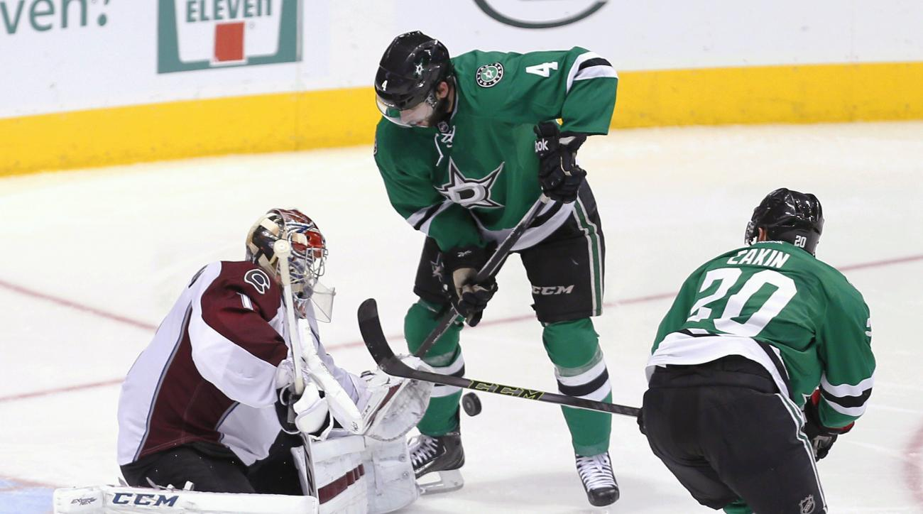 Dallas Stars forward Cody Eakin (20) and defenseman Jason Demers (4) look to play a rebound off of Colorado Avalanche goalie Semyon Varlamov (1) during the third period of an NHL hockey game Saturday, Jan. 23, 2016, in Dallas. (AP Photo/Brandon Wade)