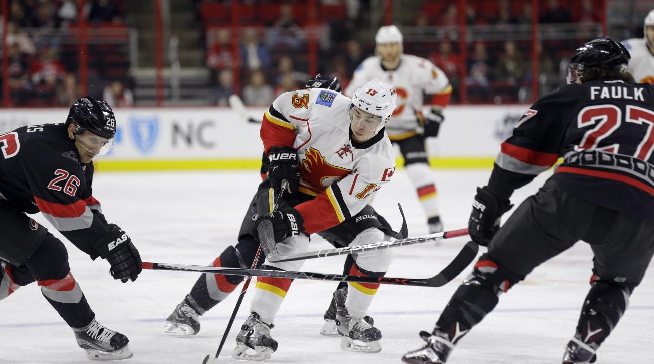 Carolina Hurricanes' John-Michael Liles (26) and Justin Faulk (27) defend against Calgary Flames' Johnny Gaudreau (13) during the first period of an NHL hockey game in Raleigh, N.C., Sunday, Jan. 24, 2016. (AP Photo/Gerry Broome)