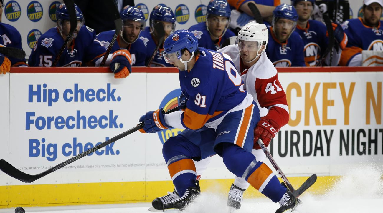 New York Islanders center John Tavares (91) fends off Detroit Red Wings center Luke Glendening (41) in the first period of an NHL hockey game in New York, Monday, Jan. 25, 2016. (AP Photo/Kathy Willens)