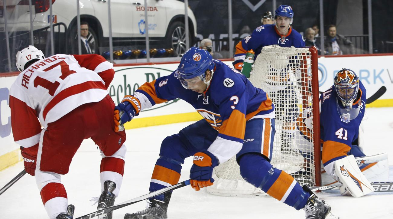 New York Islanders defenseman Travis Hamonic (3) defends as Detroit Red Wings center Brad Richards (17) goes after the puck with New York Islanders goalie Jaroslav Halak (41) of the Czech Republic looking on from the crease in the third period of an NHL h