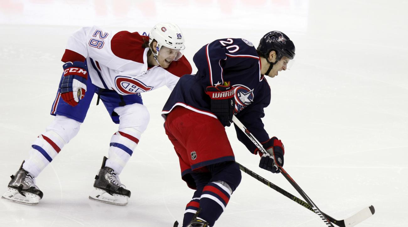 Columbus Blue Jackets' Brandon Saad, right, works for the puck against Montreal Canadiens' Jeff Petry during the third period of an NHL hockey game in Columbus, Ohio, Monday, Jan. 25, 2016. The Blue Jackets won 5-2. (AP Photo/Paul Vernon)
