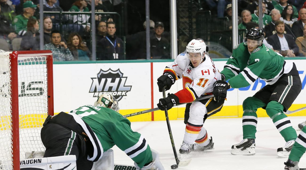 Calgary Flames center Mikael Backlund (11) of Sweden attempts to get the puck into the net past Dallas Stars' Antti Niemi (31) of Finland as John Klingberg (3) of Sweden helps defend against the shot in the second period of an NHL hockey game, Monday, Jan