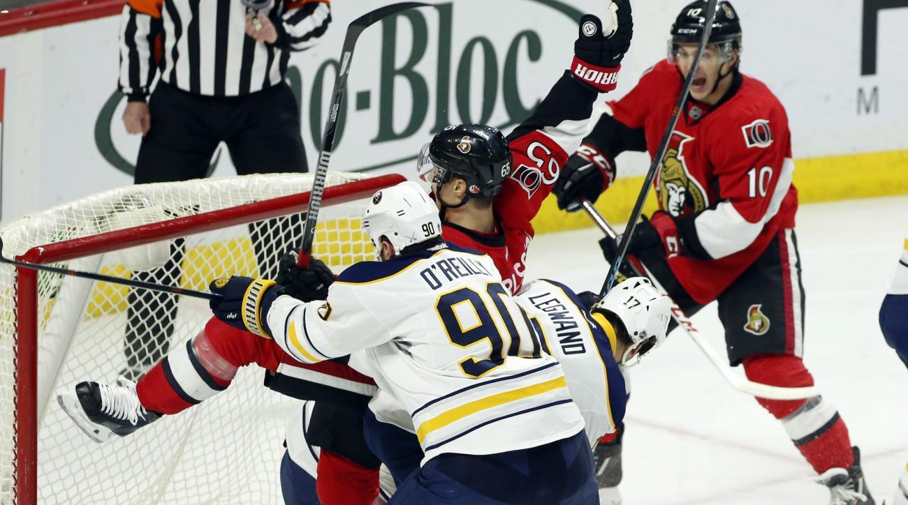 Ottawa Senators' Erik Karlsson (65) scores as he slides into the net with Buffalo Sabres' Ryan O'Reilly (90) and David Legwand (17) in tow as Ottawa Senators' Shane Prince (10) celebrates the goal during first period NHL hockey action in Ottawa, Ontario,