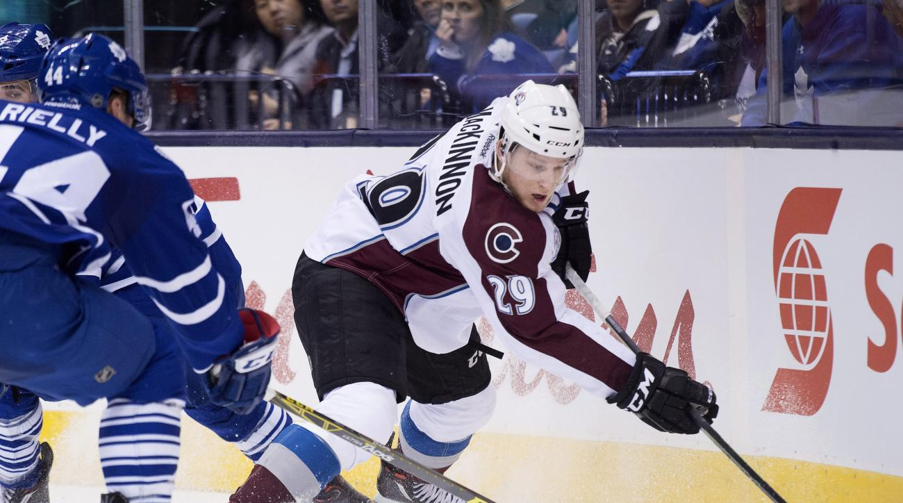 FILE - In this Nov. 17, 2015, file photo, Colorado Avalanche center Nathan MacKinnon (29) battles for the loose puck against Toronto Maple Leafs defenseman Morgan Rielly (44) during the first period of an NHL hockey game in Toronto. In the days and weeks