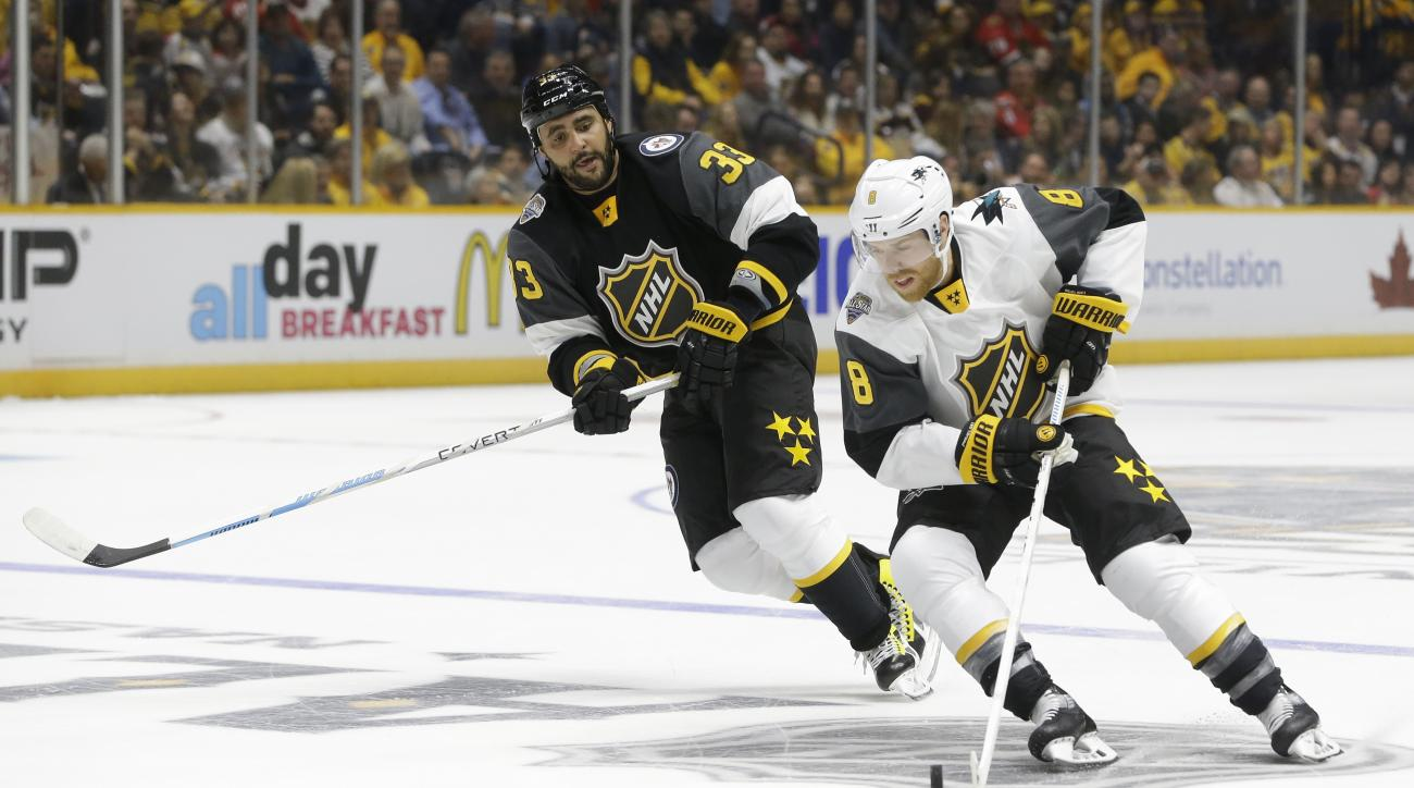 Pacific Division defenseman Drew Doughty (8), of the Los Angeles Kings, moves the puck against Central Division defenseman Dustin Byfuglien (33), of the Winnipeg Jets, during an NHL hockey All-Star semifinal round game Sunday, Jan. 31, 2016, in Nashville,