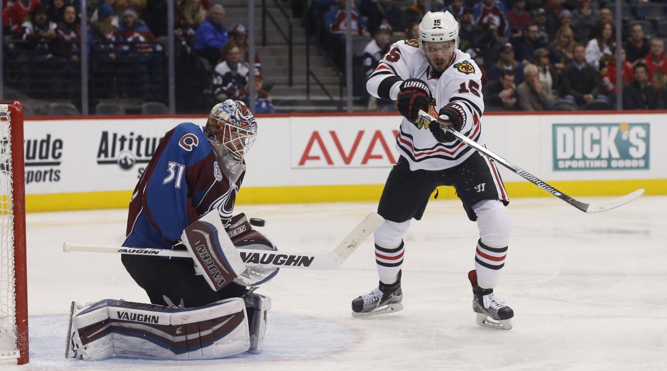 Chicago Blackhawks center Artem Anisimov, right, of Russia, redirects a shot toward Colorado Avalanche goalie Calvin Pickard during the second period of an NHL hockey game Tuesday, Feb. 2, 2016, in Denver. (AP Photo/David Zalubowski)