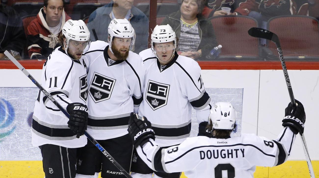 Los Angeles Kings' Jake Muzzin, second from left, celebrates his goal against the Arizona Coyotes with Anze Kopitar (11), of Slovenia; Drew Doughty (8); and Tyler Toffoli (73) during the second period of an NHL hockey game Tuesday, Feb. 2, 2016, in Glenda