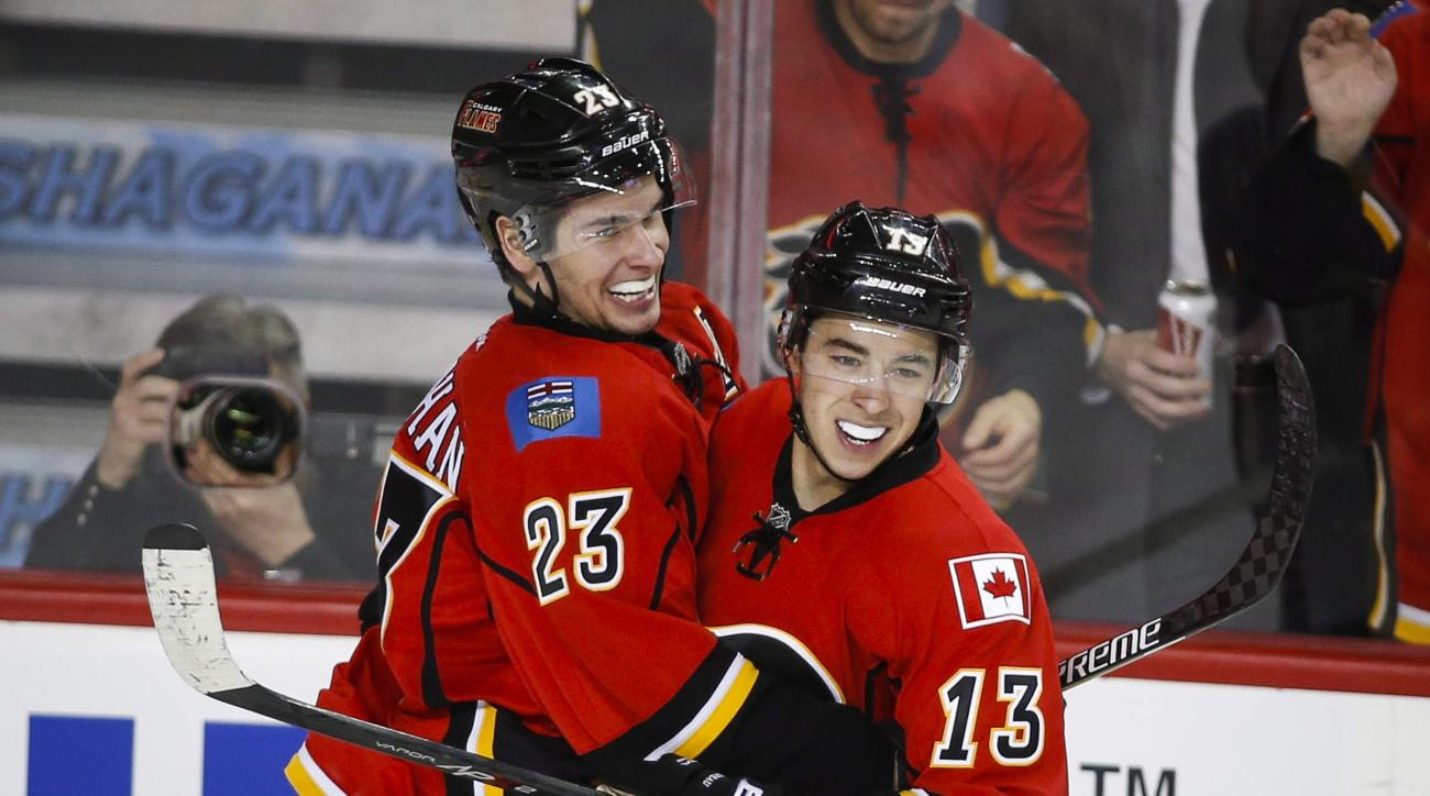 Calgary Flames' Sean Monahan, left, celebrates his goal with teammate Johnny Gaudreau during the third period against the Carolina Hurricanes in an NHL hockey game Wednesday, Feb. 3, 2016, in Calgary, Alberta. (Jeff McIntosh/The Canadian Press via AP)