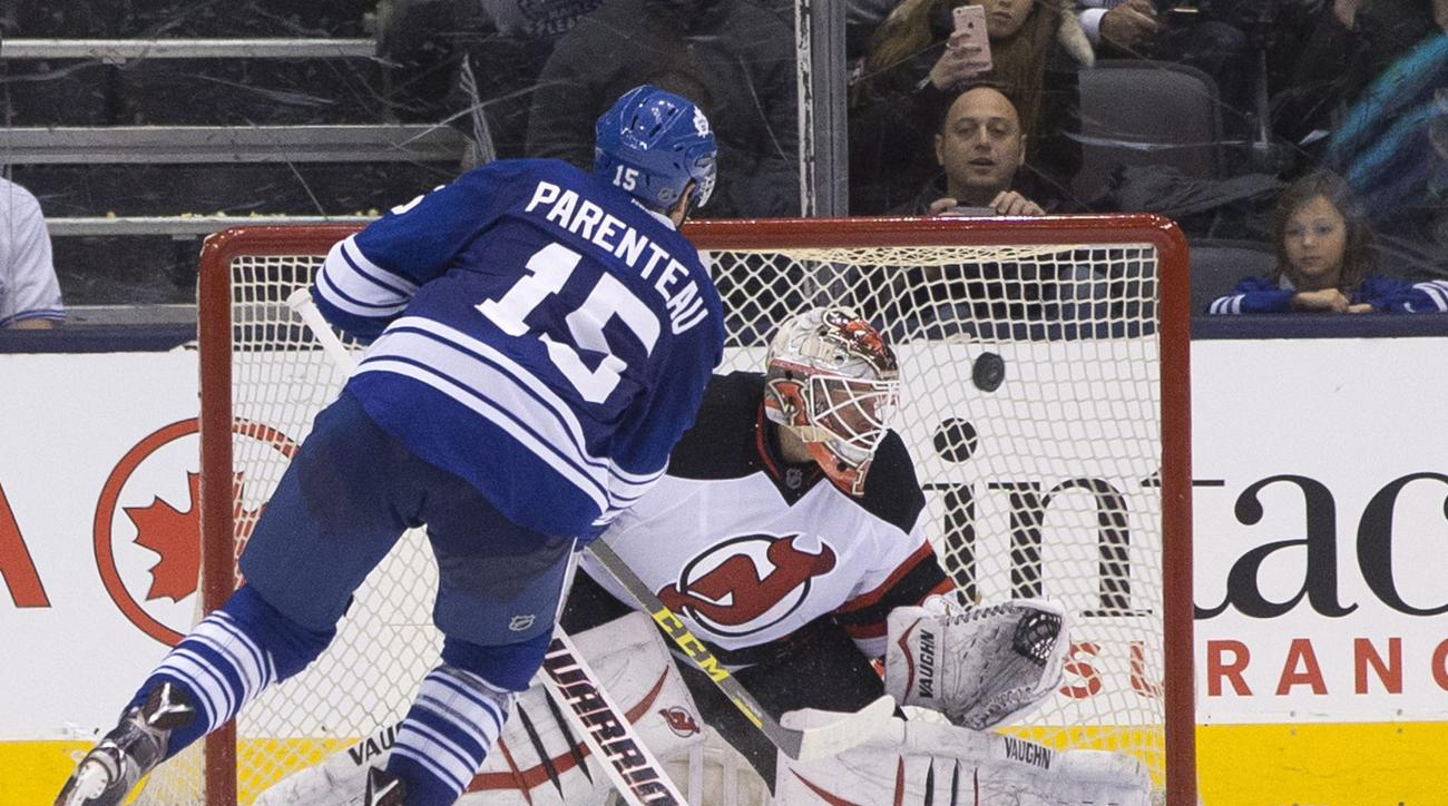 Toronto Maple Leafs' Pierre-Alexandre Parenteau (15) scores on New Jersey Devils goaltender Keith Kinkaid during the shootout in an NHL hockey game Thursday, Feb. 4, 2016, in Toronto. Toronto won 3-2. (Chris Young/The Canadian Press via AP)