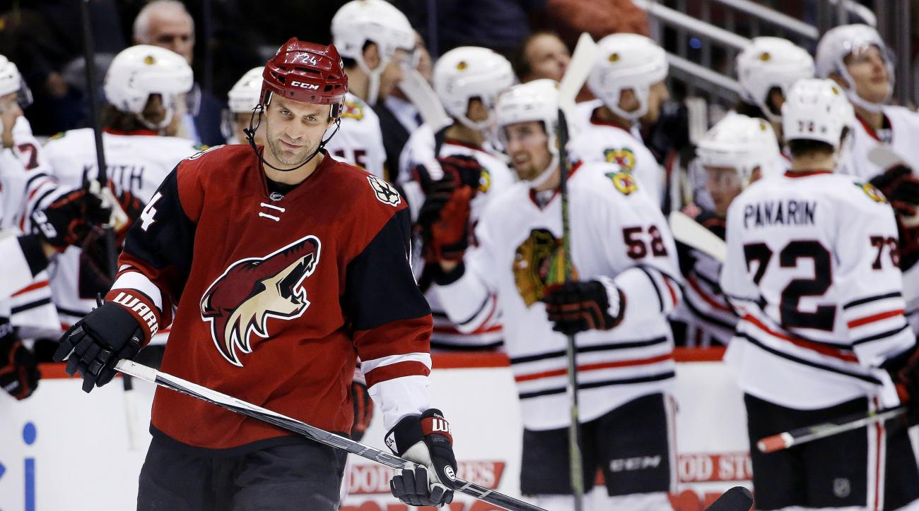 Arizona Coyotes' Kyle Chipchura, left, skates away as Chicago Blackhawks' Erik Gustafsson (52), of Sweden, and Artemi Panarin (72), of Russia, celebrate a goal by Jonathan Toews during the second period of an NHL hockey game Thursday, Feb. 4, 2016, in Gle