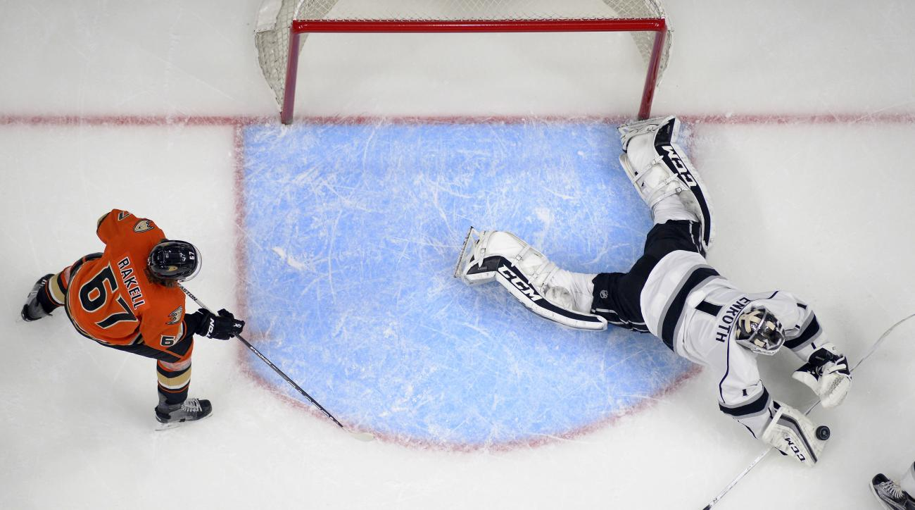 Los Angeles Kings goalie Jhonas Enroth, of Sweden, dives on the puck as Anaheim Ducks center Rickard Rakell, of Sweden, stands by during the second period of an NHL hockey game Thursday, Feb. 4, 2016, in Los Angeles. (AP Photo/Mark J. Terrill)