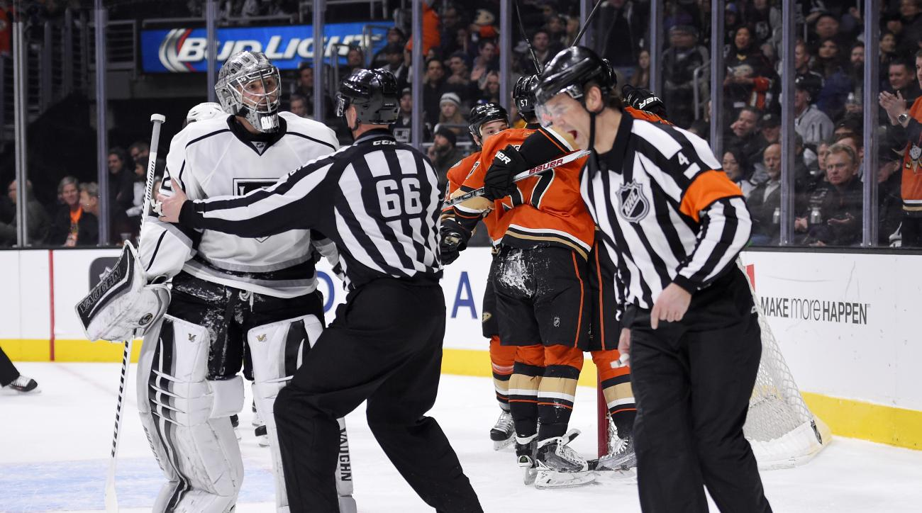 FILE - In this Feb. 4, 2016 file photo, Los Angeles Kings goalie Jonathan Quick, left, is held back away from referee Wes McCauley, right, by linesman Darren Gibbs after Anaheim Ducks left wing David Perron scored on Quick during the first period of an NH