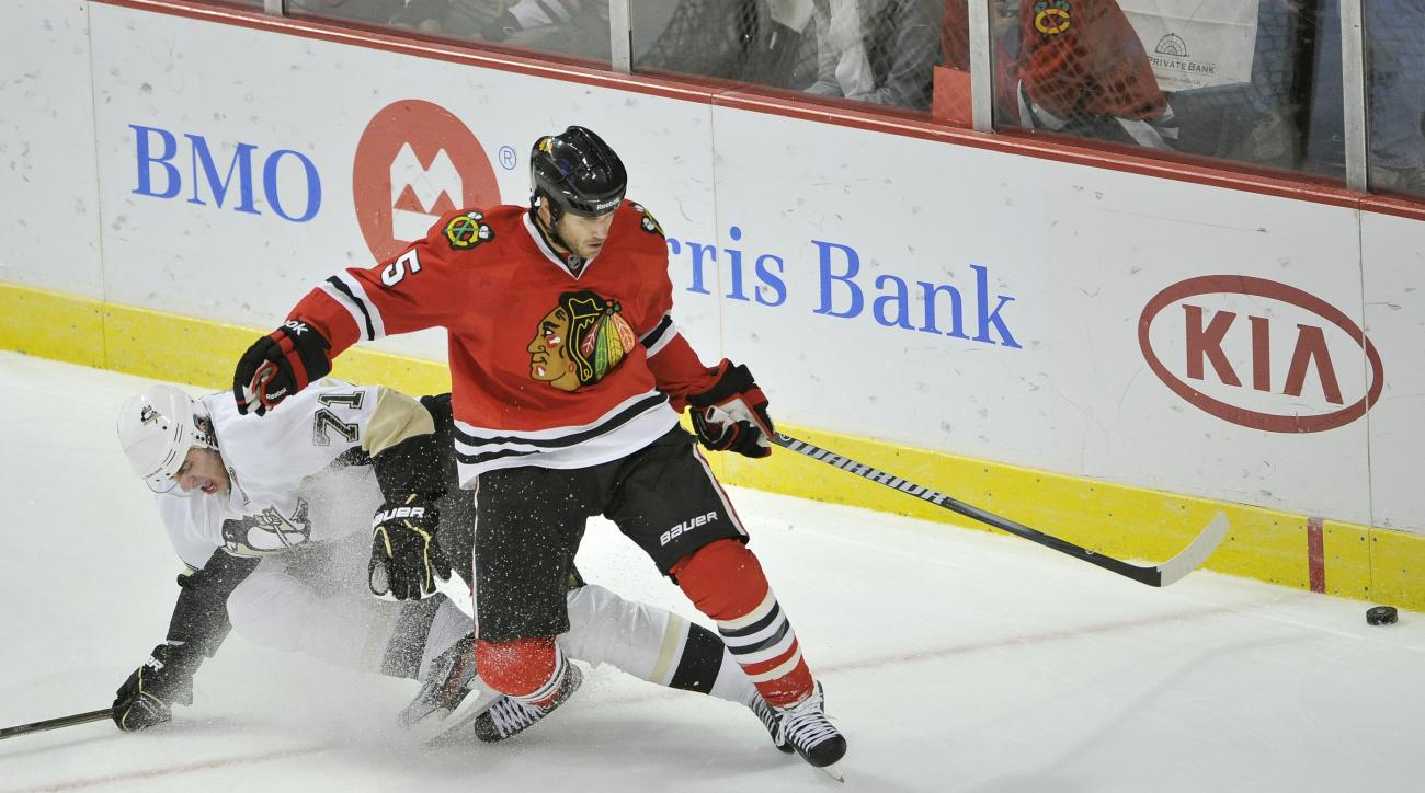 FILE - In this Sept. 30, 2011 file photo, Chicago Blackhawks defenseman Steve Montador, right, and Pittsburgh Penguins center Evgeni Malkin, of Russia, go for the puck during the first period of a preseason NHL hockey game, in Chicago. Montador is among a