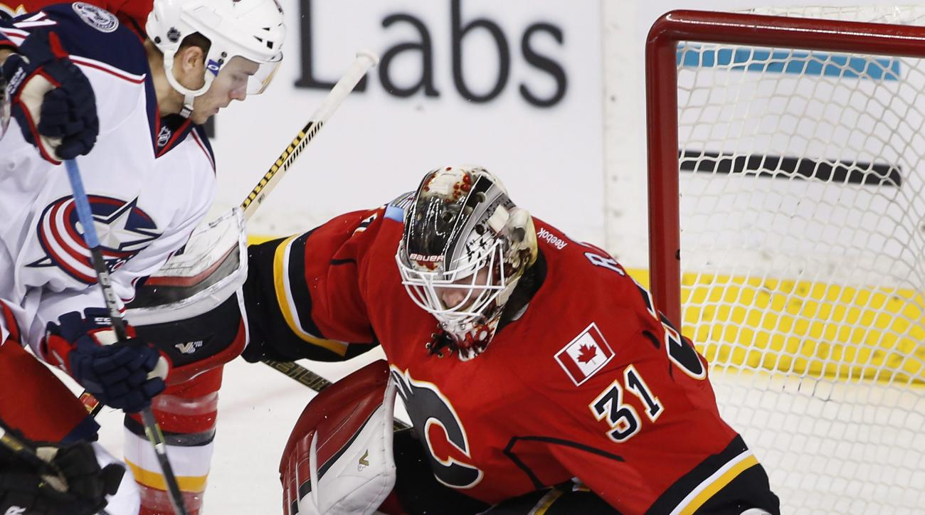 Calgary Flames goalie Karri Ramo, right, from Finland, makes a save against Columbus Blue Jackets' Alexander Wennberg, from Sweden, during the first period of an NHL hockey game, Friday, Feb. 5, 2016 in Calgary, Alberta. (Larry MacDougal/The Canadian Pres