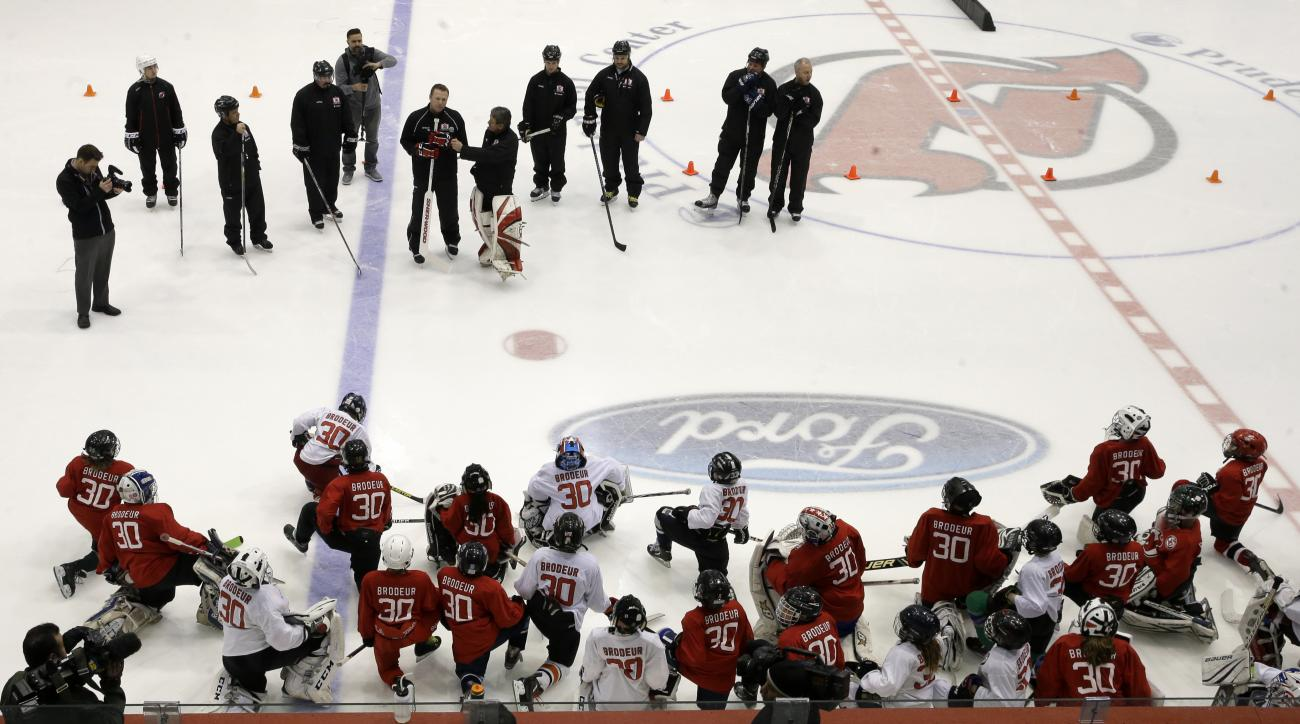 "As a large group of children wearing Martin Brodeur jerseys listen as retired New Jersey Devils goalie Martin Brodeur, center left, and former goalie Glenn Allan ""Chico"" Resch, center right, start a hockey camp before an NHL hockey game between the Devils"