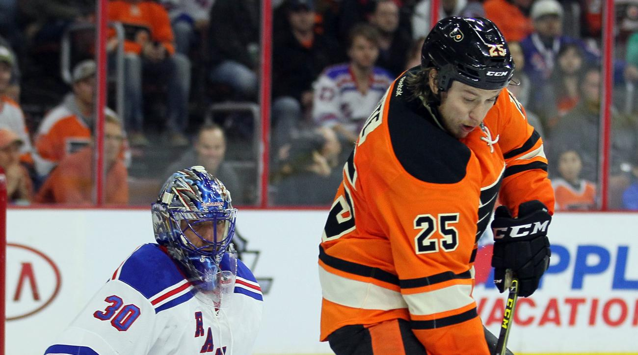 Philadelphia Flyers' Ryan White, right, who scored both of the Flyers' goals, gets a puck on his stick in front of New York Rangers goalie Henrik Lundqvist during the second period of an NHL hockey game Saturday, Feb. 6, 2016 in Philadelphia. The Rangers