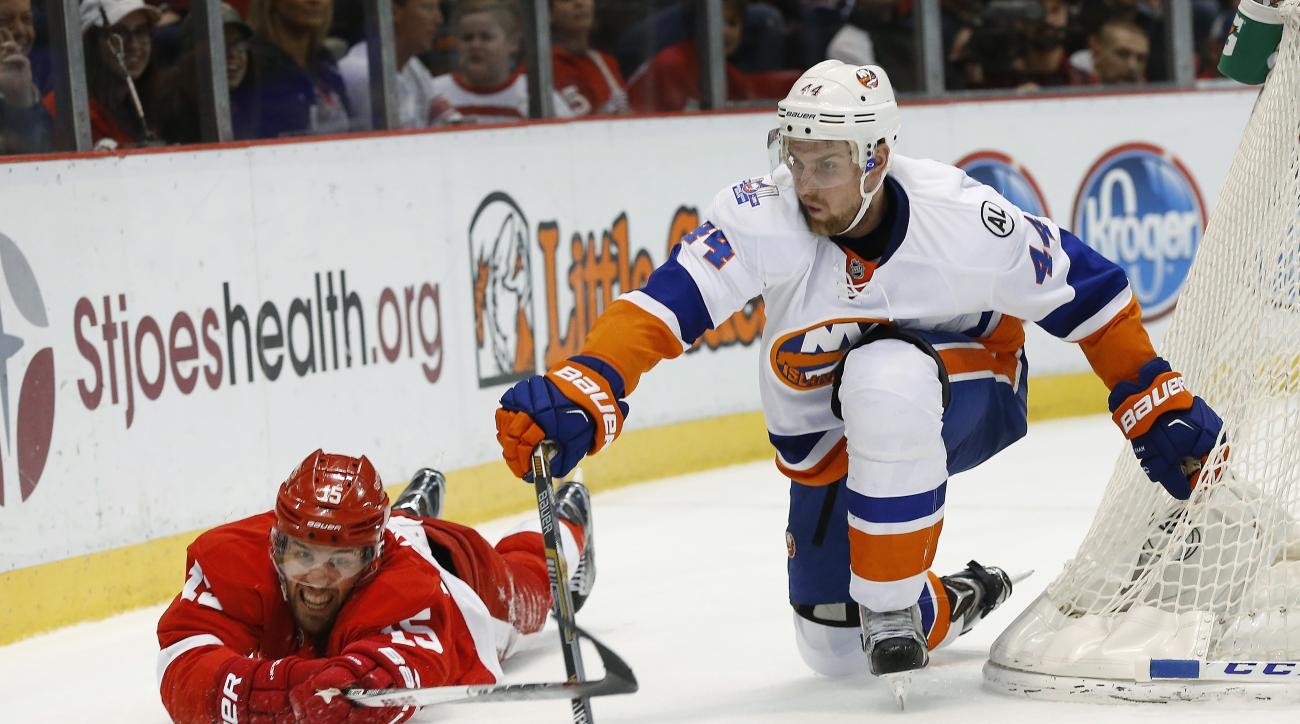 Detroit Red Wings center Riley Sheahan and New York Islanders defenseman Calvin de Haan (44) reach for the puck in the second period of an NHL hockey game Saturday, Feb. 6, 2016 in Detroit. (AP Photo/Paul Sancya)