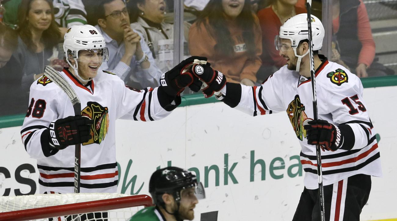 Chicago Blackhawks right wing Patrick Kane (88) celebrates scoring his goal with teammate Chicago Blackhawks center Artem Anisimov (15) as Dallas Stars defenseman Alex Goligoski (33) skates off during the second period of an NHL hockey game Saturday, Feb.