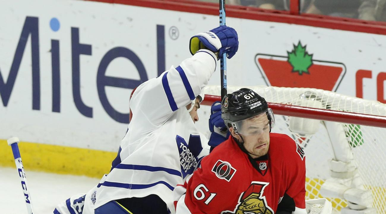 Ottawa Senators' Mark Stone (61) reacts after being hit by the puck as he screens Toronto Maple Leafs' goalie Jonathan Bernier (45) as teammate Roman Polak (46) reacts during the second period of an NHL hockey game, Saturday, Feb. 6, 2016, in Ottawa, Onta