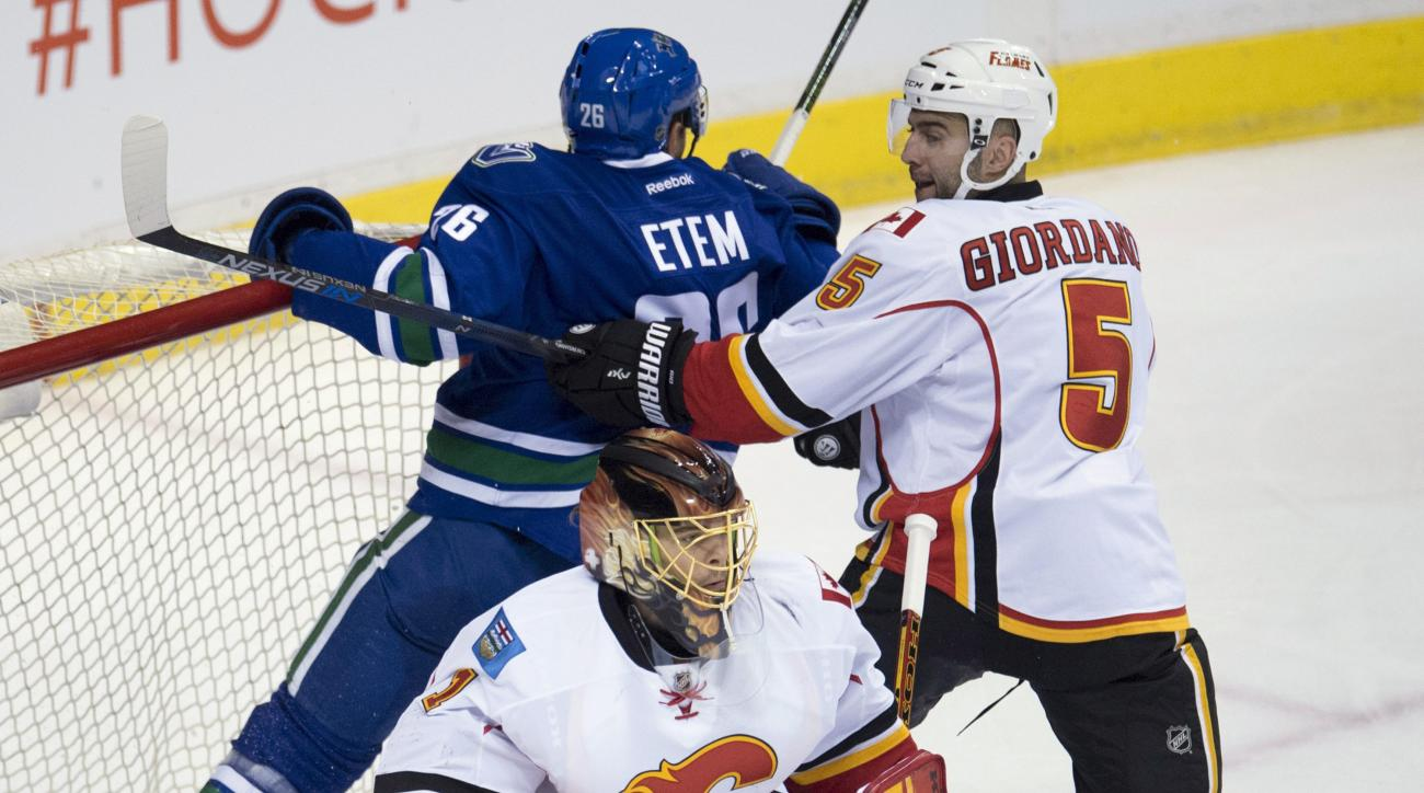 Calgary Flames defenseman Mark Giordano (5) tries to clear Vancouver Canucks right wing Emerson Etem (26) from behind Flames goalie Jonas Hiller (1) during the first period of an NHL hockey game Saturday, Feb. 6, 2016, in Vancouver, British Columbia. (Jon