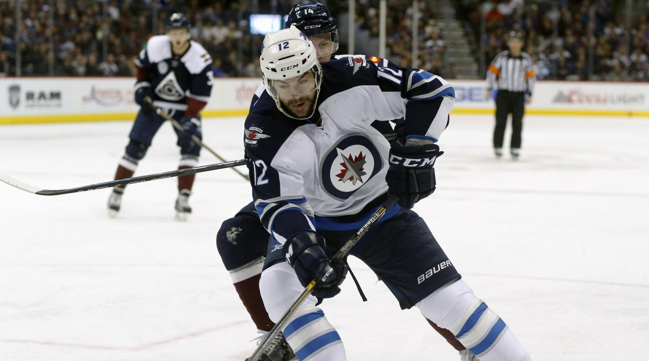 Winnipeg Jets right wing Drew Stafford, front, shoots in front of Colorado Avalanche left wing Blake Comeau in the second period of an NHL hockey game Saturday, Feb. 6, 2016, in Denver. (AP Photo/David Zalubowski)