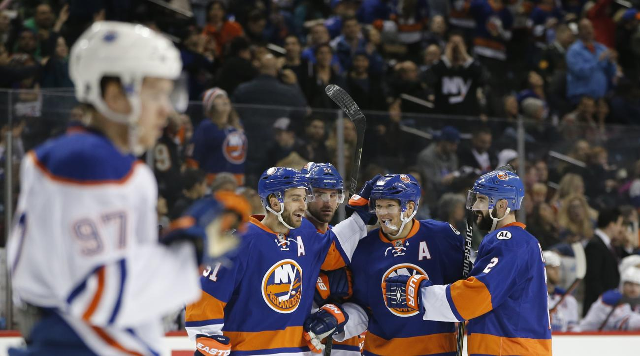 Edmonton Oilers center Connor McDavid (97) skates away as New York Islanders teammates celebrate with right wing Kyle Okposo (21) after Okposo scored a goal in the second period of an NHL hockey game in New York, Sunday, Feb. 7, 2016. (AP Photo/Kathy Will