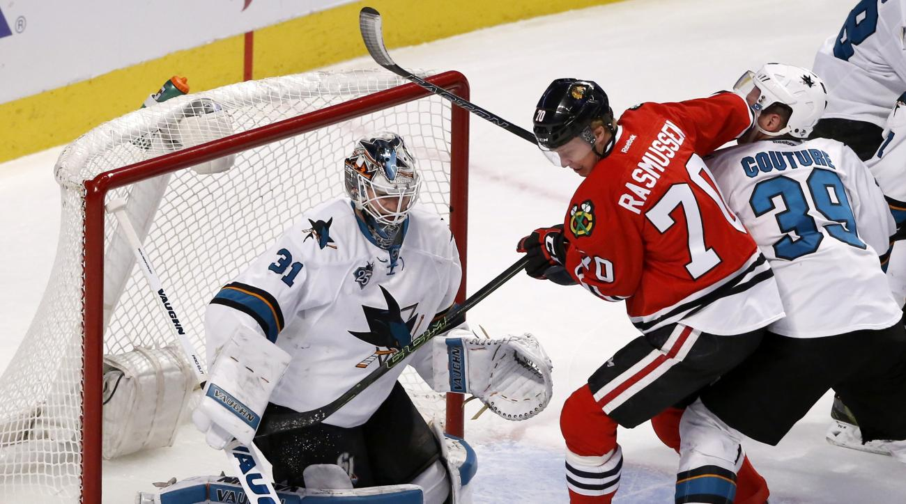Chicago Blackhawks left wing Dennis Rasmussen (70) is unable to get a shot on San Jose Sharks goalie Martin Jones (31) as Logan Couture also defends during the first period of an NHL hockey game Tuesday, Feb. 9, 2016, in Chicago. (AP Photo/Charles Rex Arb