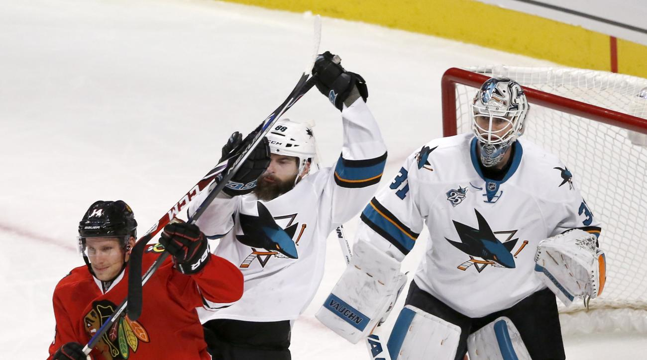 Chicago Blackhawks right wing Richard Panik, left, and San Jose Sharks defenseman Brent Burns, center, battle for position in front of goalie Martin Jones during the second period of an NHL hockey game Tuesday, Feb. 9, 2016, in Chicago. (AP Photo/Charles