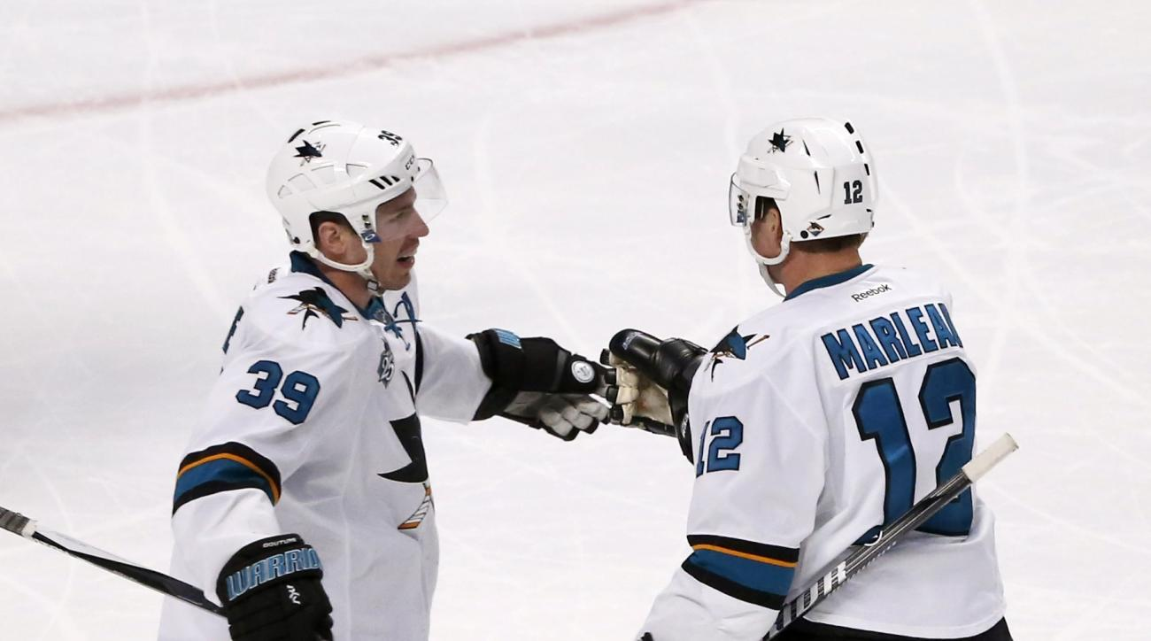 San Jose Sharks center Logan Couture (39) celebrates with Patrick Marleau Marleau's goal during the second period of an NHL hockey game against the Chicago Blackhawks Tuesday, Feb. 9, 2016, in Chicago. (AP Photo/Charles Rex Arbogast)