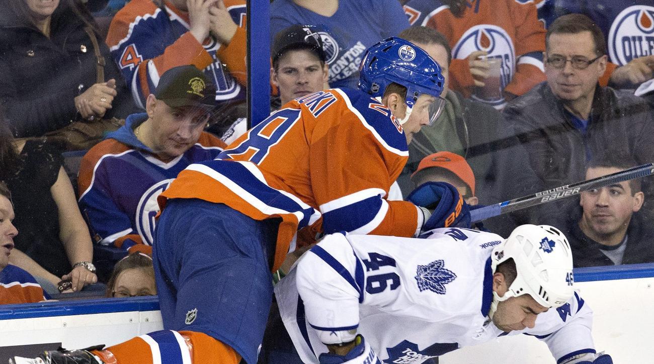 Toronto Maple Leafs' Roman Polak (46) checks Edmonton Oilers' Lauri Korpikoski (28) during the second period of an NHL hockey game, Thursday, Feb. 11 2016, in Edmonton, Alberta.  (Jason Franson/The Canadian Press via AP) MANDATORY CREDIT