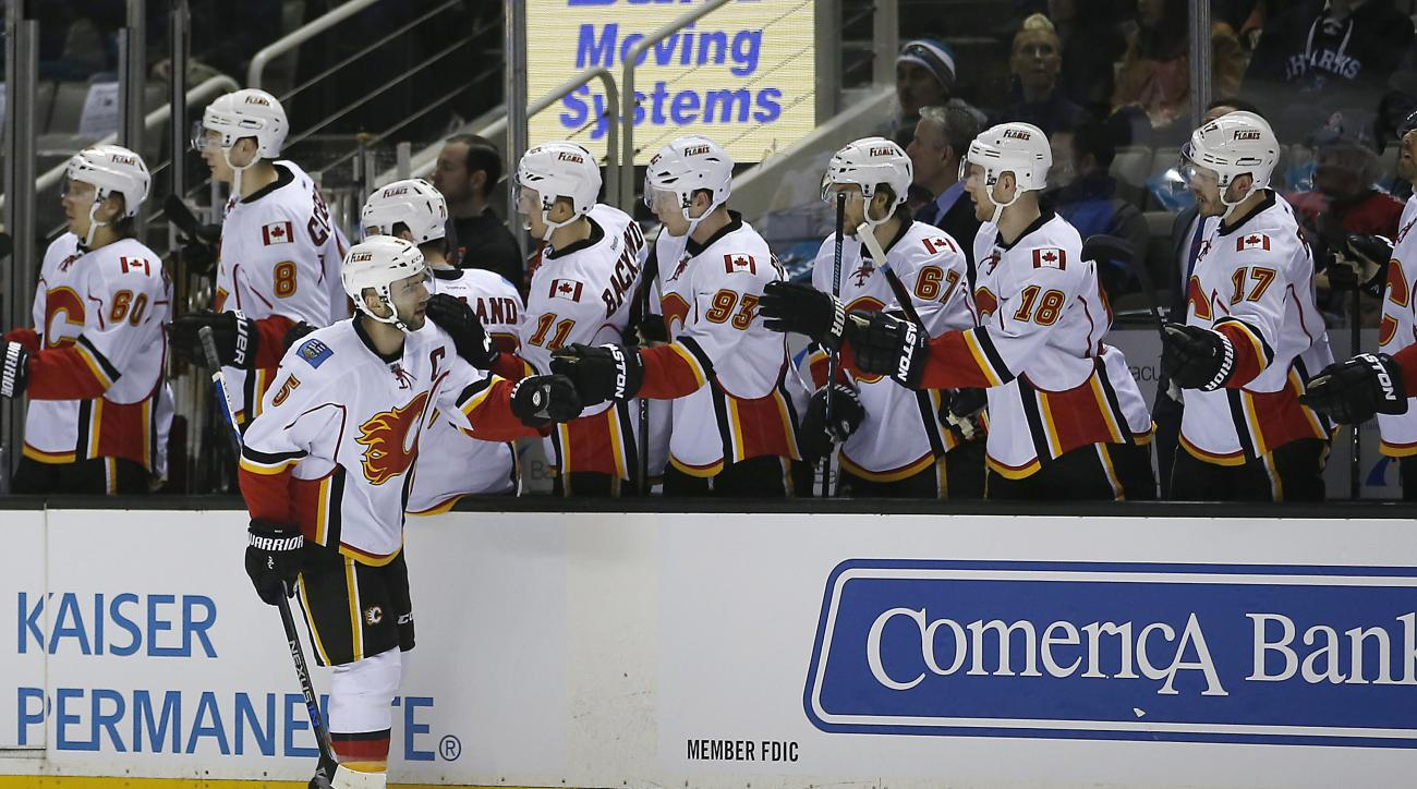 Calgary Flames defenseman Mark Giordano (5) celebrates with his teammates after scoring a goal against the San Jose Sharks during the first period of an NHL hockey game in San Jose, Calif., Thursday, Feb. 11, 2016. (AP Photo/Tony Avelar)