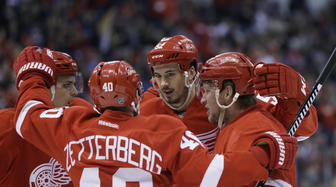 Detroit Red Wings left wing Henrik Zetterberg (40), of Sweden, congratulates defenseman Jonathan Ericsson, center, of Sweden, after Ericsson scored a goal during the second period of an NHL hockey game against the Colorado Avalanche, Friday, Feb. 12, 2016