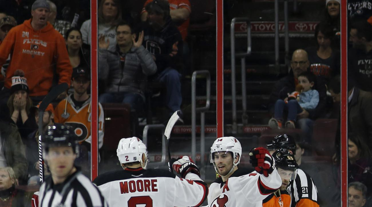 New Jersey Devils' Adam Henrique (14) celebrates with John Moore (2) past Philadelphia Flyers' Nick Schultz (55) after Henrique's game-winning goal during overtime of an NHL hockey game, Saturday, Feb. 13, 2016, in Philadelphia. New Jersey won 2-1. (AP Ph