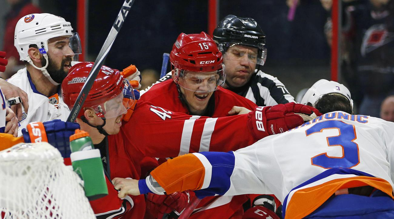 Carolina Hurricanes' Joakim Nordstrom (42) of Sweden, and Andrej Nestrasil (15) of the Czech Republic, tussle with New York Islanders' Travis Hamonic (3) during the second period of an NHL hockey game, Saturday, Feb. 13, 2016, in Raleigh, N.C. (AP Photo/K