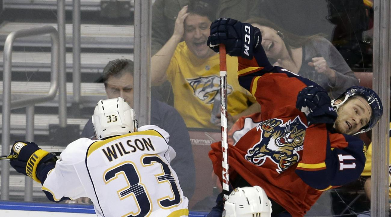 Nashville Predators center Colin Wilson (33) checks Florida Panthers center Jonathan Huberdeau (11) during the second period of an NHL hockey game, Saturday, Feb. 13, 2016, in Sunrise, Fla. (AP Photo/Alan Diaz)