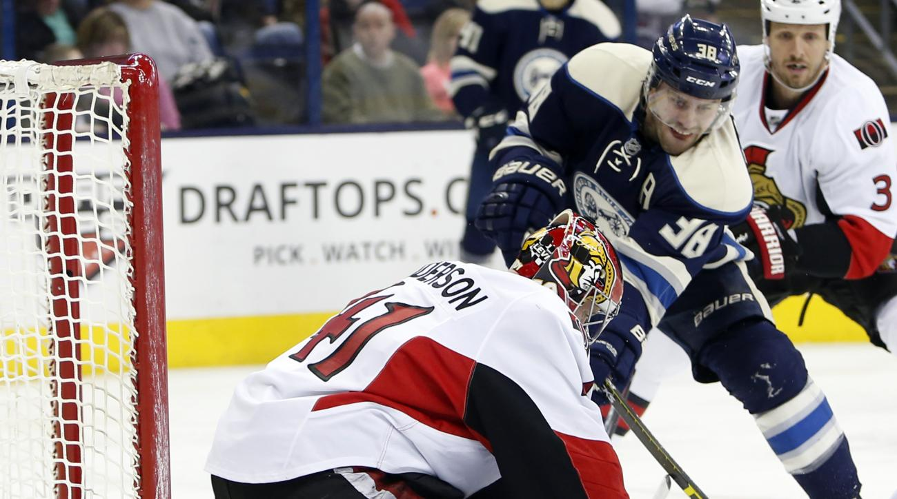 Ottawa Senators' Craig Anderson, left, makes a save against Columbus Blue Jackets' Boone Jenner during the second period of an NHL hockey game Saturday, Feb. 13, 2016, in Columbus, Ohio. (AP Photo/Jay LaPrete)