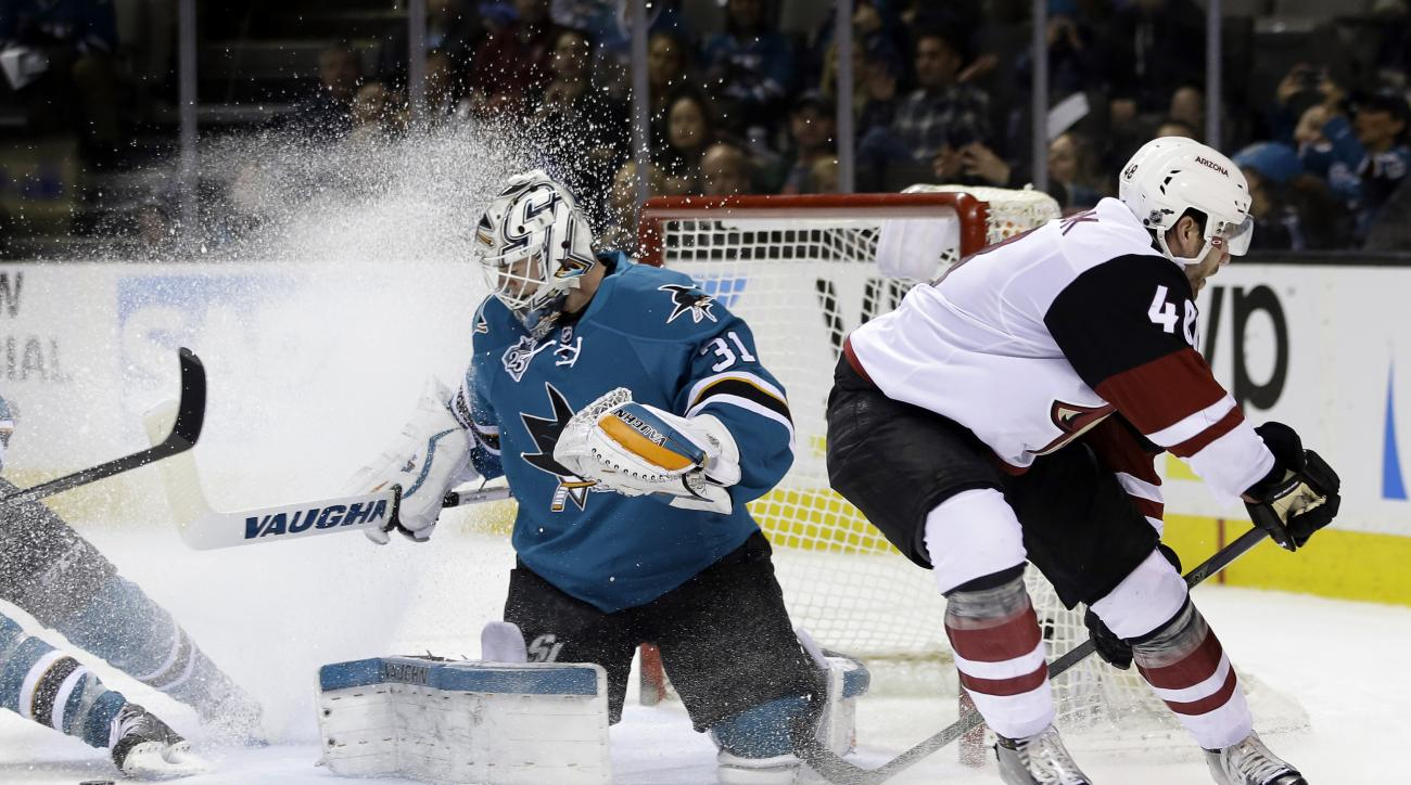 San Jose Sharks goalie Martin Jones, left, stops a shot from Arizona Coyotes' Jordan Martinook, right, during the second period of an NHL hockey game Saturday, Feb. 13, 2016, in San Jose, Calif. (AP Photo/Marcio Jose Sanchez)