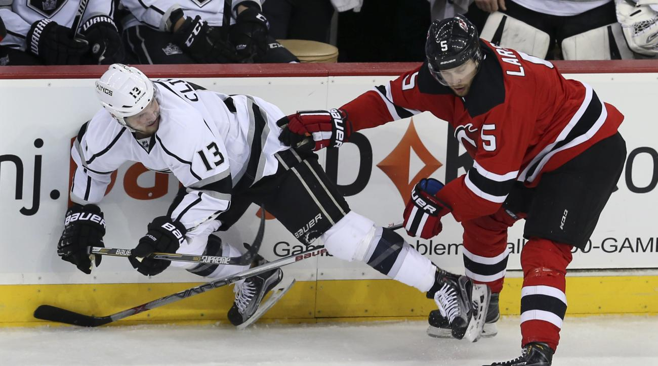 New Jersey Devils defenseman Adam Larsson (5), of Sweden, knocks down Los Angeles Kings left wing Kyle Clifford (13) during the second period of an NHL hockey game Sunday, Feb. 14, 2016, in Newark N.J. (AP Photo/Mel Evans)
