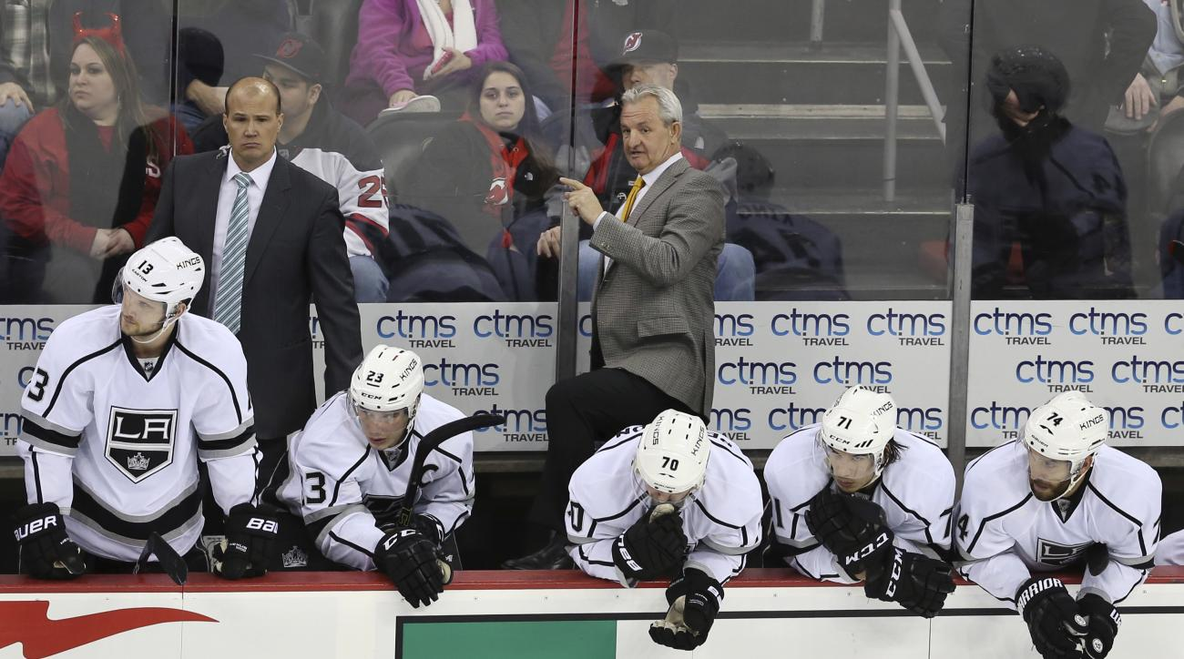 Los Angeles Kings head coach Darryl Sutter, center, talks to his players during the third period of an NHL hockey game against the New Jersey Devils Sunday, Feb. 14, 2016, in Newark N.J.  The Devils won 1-0. (AP Photo/Mel Evans)