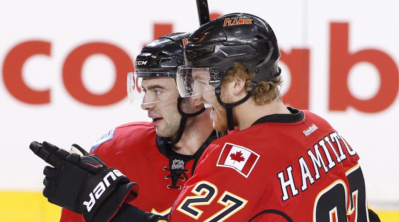 Calgary Flames' Dougie Hamilton, right, celebrates with Mark Giordano after scoring against the Anaheim Ducks during first period NHL action in Calgary, Alberta, Monday, Feb. 15, 2016. (Larry MacDougal/The Canadian Press via AP) MANDATORY CREDIT